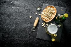 Beer in a glass and a bottle of peanuts in a bowl. On black rustic background royalty free stock photography