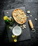 Beer in a glass and a bottle of peanuts in a bowl. On black rustic background stock photos