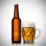 Beer in glass and bottle on white Royalty Free Stock Photography