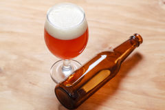 Beer glass and bottle on wood Stock Images