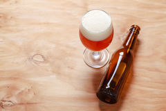 Beer glass and bottle on wood Royalty Free Stock Images