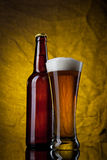 Beer in glass with bottle on yellow Stock Image