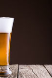 Beer glass in a brown background. Stock Photography