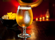 Beer glass and chips in elegant restaurant or pub interior. Beer glass and potato chips in elegant restaurant, pub or cocktail bar interior Royalty Free Stock Photography