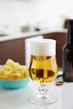 Beer glass with chips Stock Photography