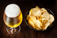 Beer glass and chips - snack bar or pub menu. Beer glass and potato chips in a black bowl on dark wood background - snack bar or pub menu Royalty Free Stock Images