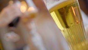 Beer glass with clinking glasses on the background out of focus stock video footage