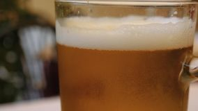 Beer glass covered in condensation perlage, bubbles rising inside.  stock footage