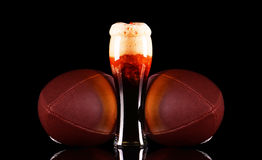 Beer glass with dark beer foam and American football ball on black background. Royalty Free Stock Image