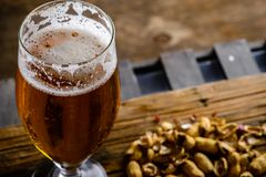 Beer glass with dark cold beer with bubble froth and peanuts on. The table royalty free stock photo