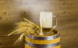 Beer glass flowing foam on wooden barrel Royalty Free Stock Photography
