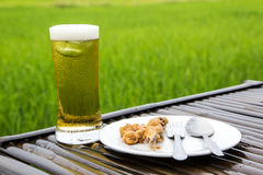 Beer glass and fried fish. On the bamboo table, Green rice field blur background stock image