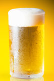 Beer glass with froth over yellow background Royalty Free Stock Photography