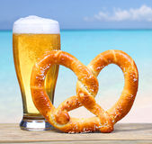 Beer Glass with German Pretzel over Ocean view. Vacation Stock Photography