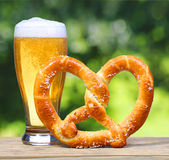 Beer Glass with German Pretzel on Wooden Table over Nature Royalty Free Stock Photos
