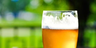 Beer in a glass glass glass, bubbles rise. On the background of green foliage glass with Golden drops. stock photos