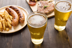 Beer in glass with gourmet steak and french fries on wooden back Royalty Free Stock Photos