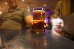 Beer glass in hand. Man sitting in a pub or bar with a glass of beer stock photography