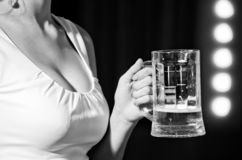 Beer glass in hand of sommelier woman. In dress near mirror with lamps, meeting and relax, bar and restaurant, tasting and degustation royalty free stock photos