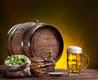 Beer glass, old oak barrel, wheat ears and hops. Beer glass, old oak barrel and wheat ears on wooden table Royalty Free Stock Photo
