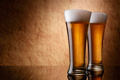 Beer into glass on a old stone Royalty Free Stock Images