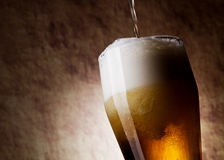 Beer into glass on a old stone background Royalty Free Stock Photos