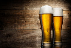 Beer into glass on a old wooden background Royalty Free Stock Photography