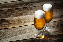 Beer into glass on a old wooden background Royalty Free Stock Image