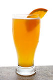 Beer in glass with orange. A beer in a glass with an orange slice on the rim Stock Photos