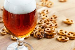 Beer glass pint with brezel. Traditional german Oktoberfest drink and food. On wooden background stock photo