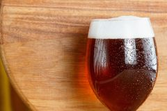 Beer glass pint with copy-space on wooden background. Mug closeup stock photography