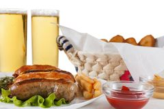 Beer glass pint with pretzels and grilled sausages. October fest, traditional menu, Beer glass pint with grilled chicken sausage with ketchup, mustard and stock image