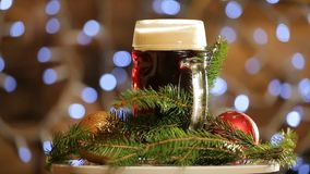 Beer in glass rotate on background with bright lights bokeh. Christmas dark beer presentation. stock footage