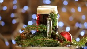 Beer in glass rotate on background with bright lights bokeh. Christmas dark beer presentation. stock video footage