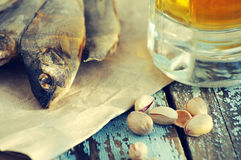 Beer in a glass, salty fish and pistachios. Beer and beer snack. Royalty Free Stock Photo
