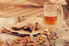 Beer in a glass, salty fish and pistachios. Beer and beer snack. Stock Photo