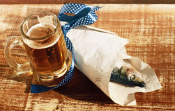 Beer in a glass, a salty herring on paper Stock Image