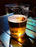 Beer Glass on a Table. Beer glass on a bar table royalty free stock photo