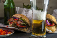 Beer glass and two hotdogs with grilled sausage and vegetables Stock Photography