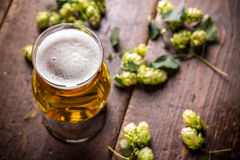 Beer into glass. On vintage wooden surface Stock Photography