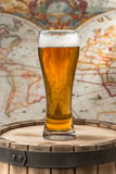Beer glass. Of beer on a wooden barrel royalty free stock photos