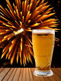 Beer glass on wooden table against of golden fireworks. royalty free stock photos