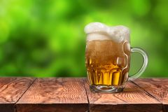 Beer in glass on wooden table against green royalty free stock photo