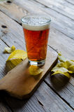 Beer into glass. On wooden table with potato chips stock image