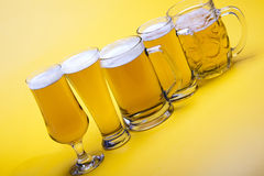 Beer glass with yellow background Royalty Free Stock Image
