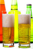 Beer glasses against bottles closeup Royalty Free Stock Image