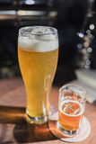 Light beer in a beer glass and dark beer in a small glass on a wooden bar counter. Vertical frame.view from above Royalty Free Stock Photos