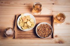 Beer glasses and beer snacks on wooden table. Vintage style. Beer glasses and beer snacks on wooden table. Drink and snack for football match or party. Vintage Stock Photography