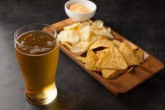 Beer in glasses closeup on the concrete table. Beer and snacks are chips and nachos with cheese souce top view. Drink and snack fo. Beer in glasses closeup on Royalty Free Stock Photography
