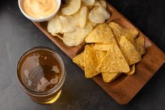 Beer in glasses closeup on the concrete table. Beer and snacks are chips and nachos with cheese souce top view. Drink and snack fo. Beer in glasses closeup on Stock Images